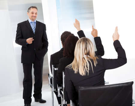 visual aid: Group of successful business people at the lecture asking questions Stock Photo