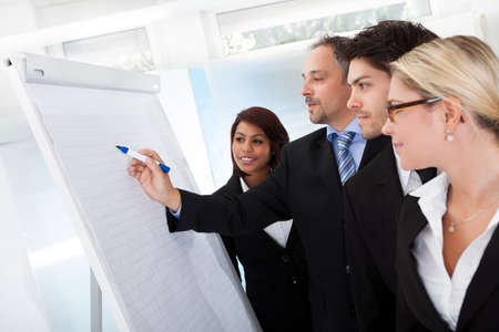 Group of business people looking at the graph on flipchart photo