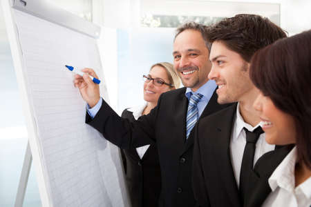flipchart: Group of business people looking at the graph on flipchart Stock Photo