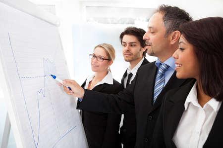 Grupo de personas de negocios que buscan en el gr�fico de la hoja de rotafolio Foto de archivo - 14314115