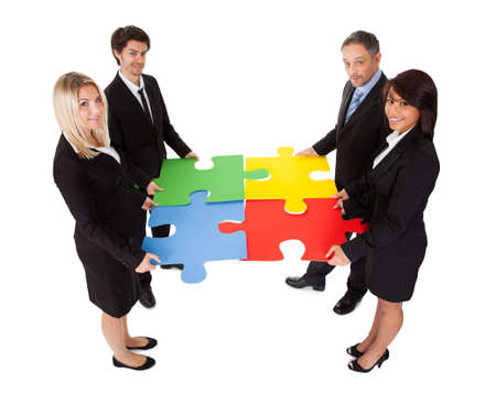 happy business team: Group of business people assembling jigsaw puzzle  Isolated on white