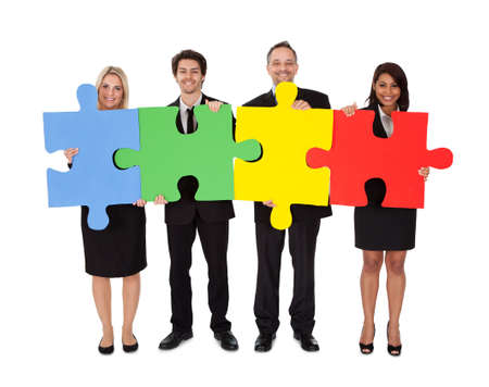 Group of business people assembling jigsaw puzzle  Isolated on white photo