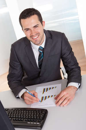 young executives: Successful businessman working at desk at the office