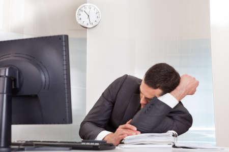 Successful businessman sleeping at desk it the office 版權商用圖片