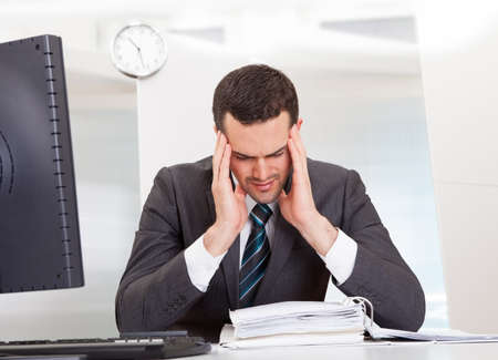 Businessman suffering from headache at the office Stock Photo - 14929218