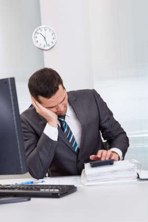 Successful businessman sleeping at desk it the office photo