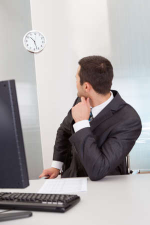 Anxious businessman looking at clock at the office photo