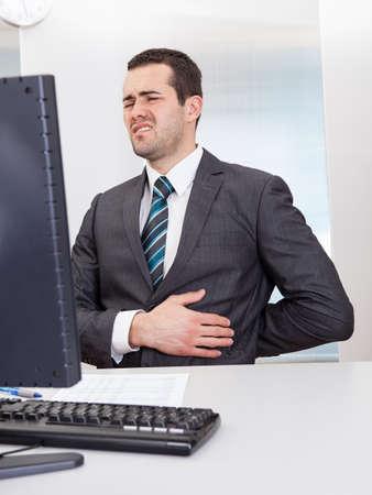 dolor de estomago: Hombre de negocios que sufre de dolor en el lugar de trabajo