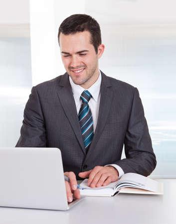 podnikatel: Úspěšný obchodník pracující u stolu v kanceláři