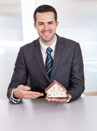 Successful businessman presenting model of the house photo