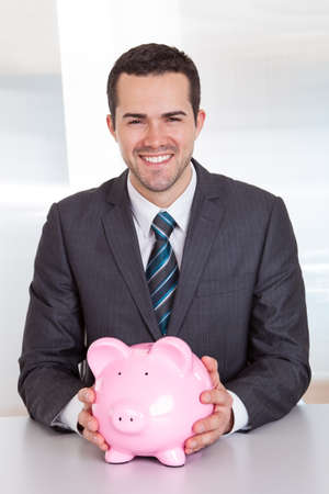 Successful businessman holding piggybank at the office photo