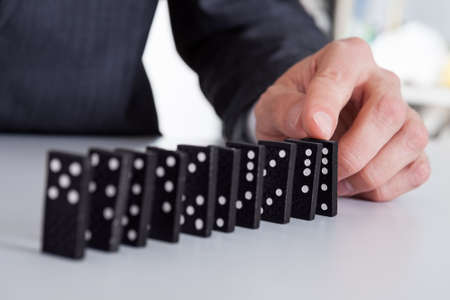 playing the market: Successful businessman playing domino at the office