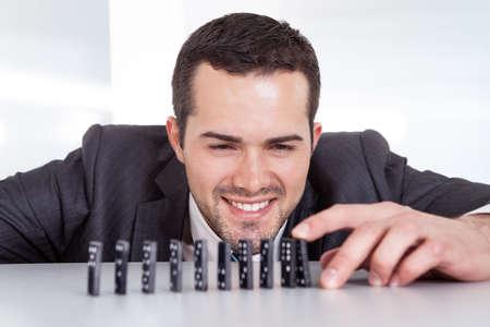 Successful businessman playing domino at the office photo