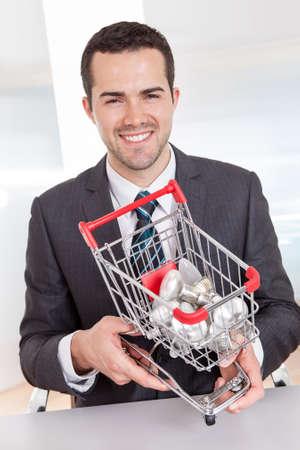 Businessman holding shopping basket full of light bulbs photo