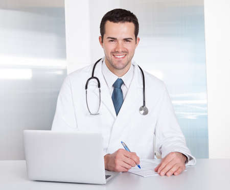 Portrait of cheerful doctor sitting at the desk working on laptop photo