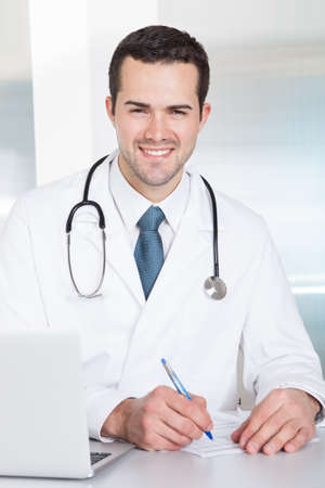 Portrait of cheerful doctor sitting at the desk working on laptop Stock Photo - 14931963