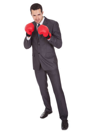 Competitive businessman in boxing gloves. Isolated on white Stock Photo - 15000573