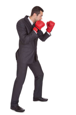 red competition: Competitive businessman in boxing gloves. Isolated on white