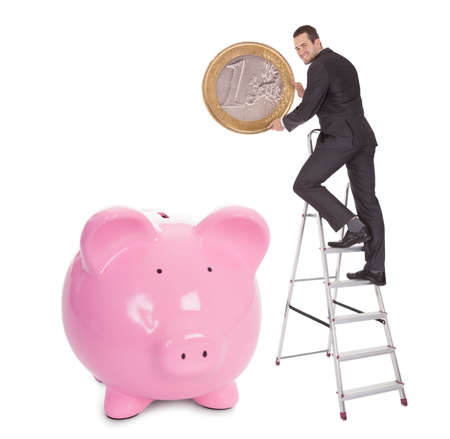 Successful businessman putting one euro coin into piggybank. Isolated on white photo