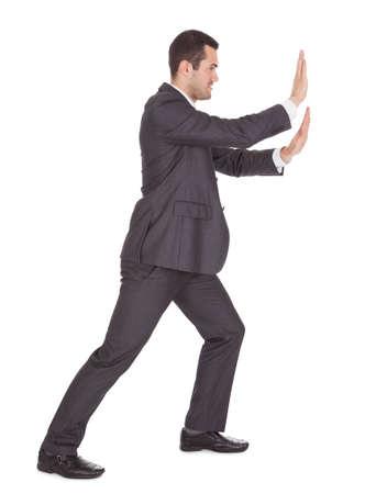 pushing: Succesvolle zakenman duwen exemplaar-ruimte. Geà ¯ soleerd op wit