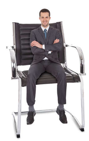 Businessman sitting in huge chair. Isolated on white