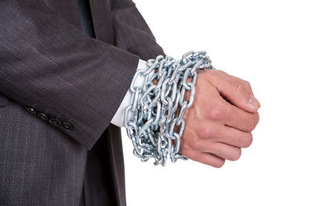 Businessman hands bound in chains. Isolated on white photo