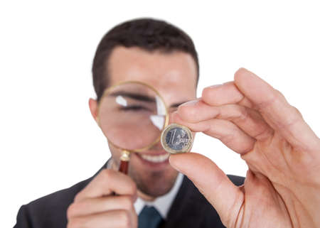 Businessman looking at one euro coin through loupe. Isolated on white Stock Photo - 14930487