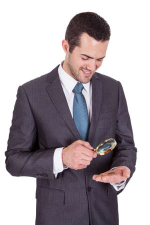 Businessman looking at one euro coin through loupe. Isolated on white photo