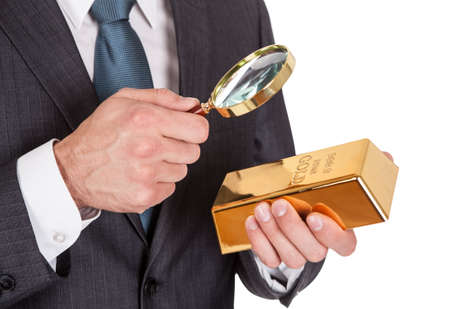 Businessman looking at gold bar through loupe. Isolated on white Stock Photo - 14929986