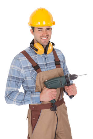 Worker holding electric drill and wearing hard hat. Isolated on white photo
