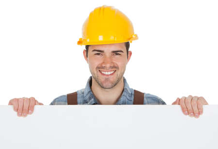 Worker wearing hard hat and holding empty banner. Isolated on white photo