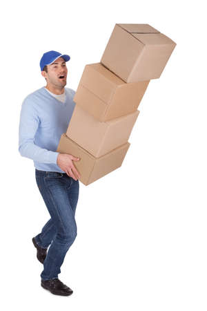 man carrying box: Young delivery man with falling stack of boxes. Isolated on white
