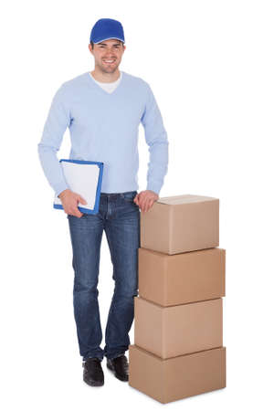 Smiling young delivery man holding stack of boxes. Isolated on white photo