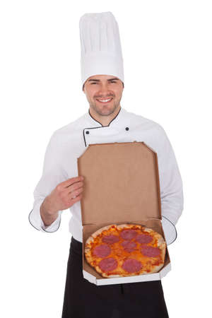 Portrait of happy chef holding pizza box. Isolated on white photo