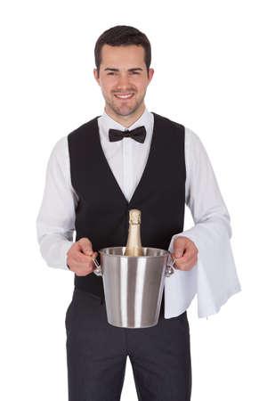 sirvientes: Mayordomo alegre sosteniendo la botella de champán. Aislados en blanco Foto de archivo