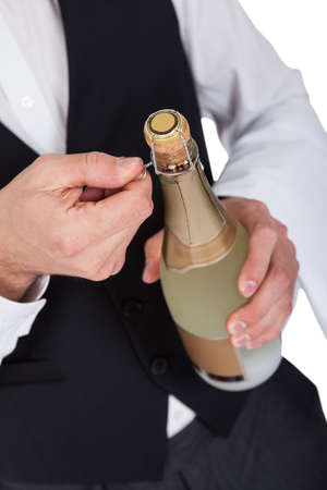 Close-up of butler opening bottle of champagne photo