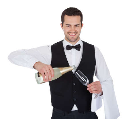 Portrait of butler pouring champagne into glass. Isolated on white photo