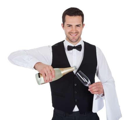camarero: Retrato de mayordomo verter champán en la copa. Aislados en blanco