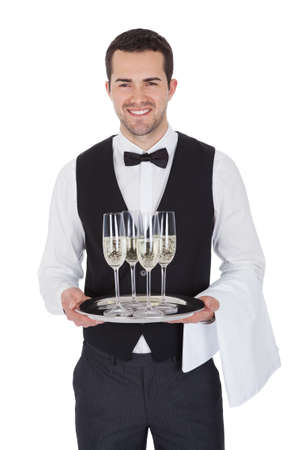 party tray: Portrait of a young butler with champagne glass. Isolated on white Stock Photo