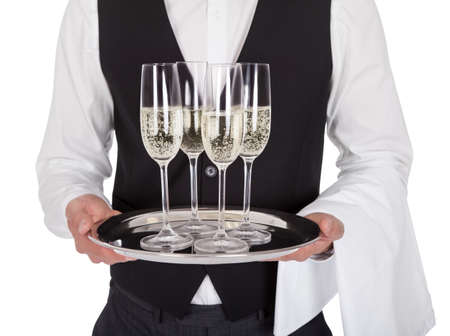 up service: Portrait of a young butler with champagne glass. Isolated on white Stock Photo