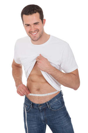 losses: Muscular young man measuring waist. Isolated on white