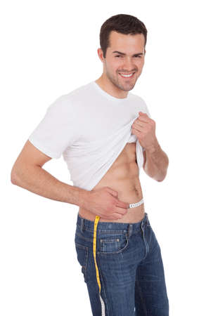 Muscular young man measuring waist. Isolated on white photo