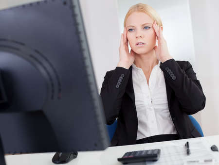 Cheerful young businesswoman with headache working in the office photo