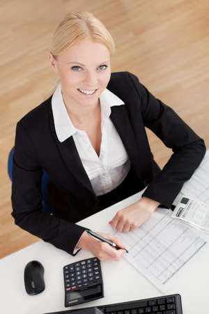 Cheerful accountant businesswoman working in the office photo