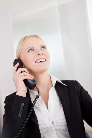 Beautiful businesswomen talking on the phone in the office photo