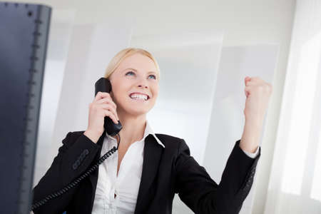 good news: Beautiful businesswomen talking on the phone in the office