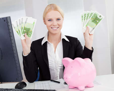 Businesswoman holding euro currency notes in the office photo