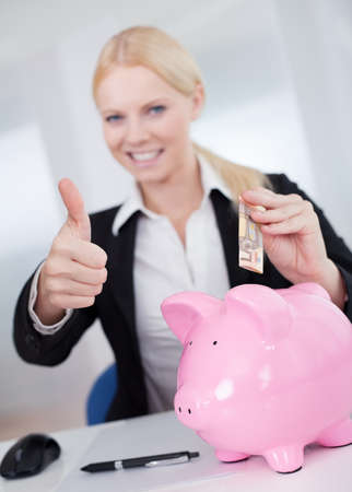 Businesswoman holding euro currency and piggybank in the office photo
