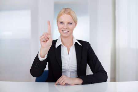 biometrics: Beautiful businesswoman touching the screen with her finger