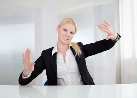 Beautiful businesswoman touching the screen with her finger Stock Photo - 15211517